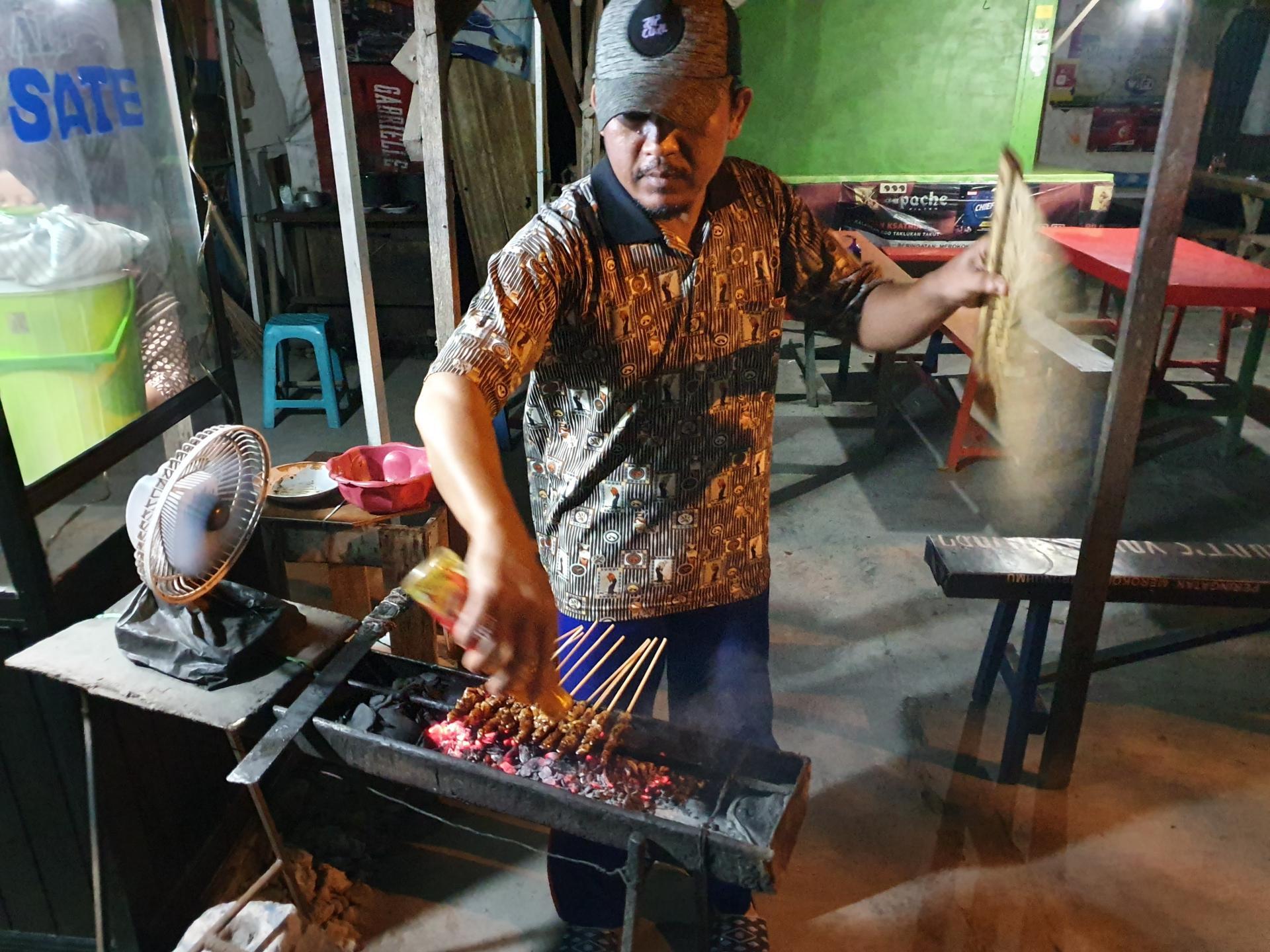 индонезиец жарит сатэ на углях