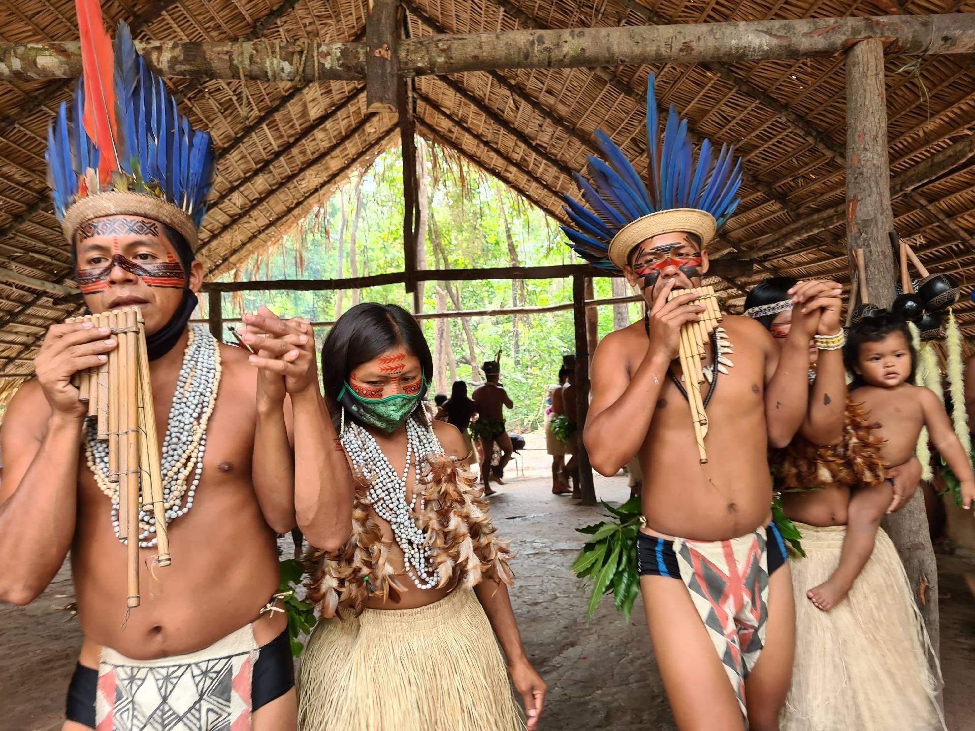 индейцы играют на духовом музыкальном инструменте из бамбука